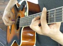 Die schwingsechziger jahre Ein Mann spielt eine Akustikgitarre mit zwei Händen c Lizenzfreie Stockfotografie