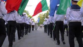 Die Seeleute, die in der Uniform gekleidet werden, gehen mit bunten Flaggen und Musikinstrumenten auf der Straße an der Parade stock video footage