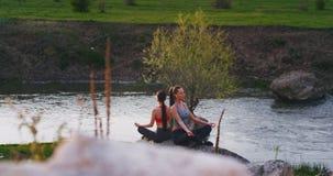 Die sehr attraktiven Damen, die Yogameditationshaltungen erhalten sie üben, Frischluft und viele Energie beim Sitzen auf einem gr