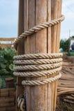 Die Seilwunde auf hölzernem Bauholz Stockbilder