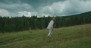 Die Seitenansicht in voller Länge des alten Mannes in der alten Kleidung, mit langem Bart gehend entlang die grünen Berge mit der stock video footage