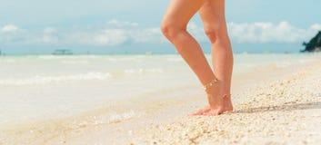 Die sexy Beine der Frauen auf den weißen Sandstrand-Sommerferien lizenzfreie stockbilder