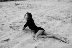 Die sexy blonde behaarte junge Frau, die in den Sanden der Wüste aufwirft, beleuchtete durch Licht der untergehenden Sonne Stockfoto