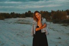 Die sexy blonde behaarte junge Frau, die in den Sanden der Wüste aufwirft, beleuchtete durch rotes Licht der untergehenden Sonne Stockfotos