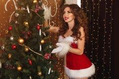 Die sexy Frau, die als Sankt gekleidet wird, verziert einen Weihnachtsbaum Stockfotos
