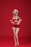 Die sexy Frau, die Weihnachtsmann trägt, kleidet mit Weihnachtsgeschenk Stockbild