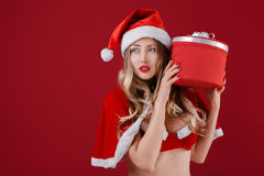 Die sexy Frau, die Weihnachtsmann trägt, kleidet mit Weihnachtsgeschenk Lizenzfreie Stockfotos