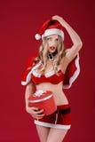 Die sexy Frau, die Weihnachtsmann trägt, kleidet mit Weihnachtsgeschenk Lizenzfreie Stockbilder