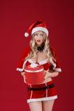 Die sexy Frau, die Weihnachtsmann trägt, kleidet mit Weihnachtsgeschenk Stockfoto