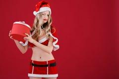 Die sexy Frau, die Weihnachtsmann trägt, kleidet mit Weihnachtsgeschenk Stockfotos