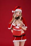 Die sexy Frau, die Weihnachtsmann trägt, kleidet mit Weihnachtsgeschenk Stockfotografie