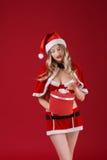 Die sexy Frau, die Weihnachtsmann trägt, kleidet mit Weihnachtsgeschenk Lizenzfreie Stockfotografie