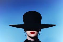 Die sexy strenge Frau mit den roten Lippen in einem Hut. Nahaufnahme-Porträt stockfotografie