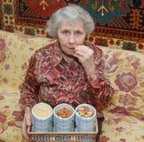 Die siebzig Einjahresfrau sitzt auf Sofa und knackt Mutter Stockfoto