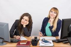 Die Situation im Büro - Träumen mit zwei Frauen, sitzend an einem Schreibtisch Lizenzfreies Stockbild