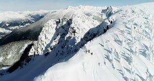 Die Skifahrer, die auf einem Schnee stehen, bedeckten Berg 4k mit einer Kappe stock footage