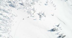 Die Skifahrer, die auf einen Schnee gehen, bedeckten Berg 4k mit einer Kappe stock footage