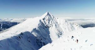 Die Skifahrer, die auf einen Schnee gehen, bedeckten Berg 4k mit einer Kappe stock video