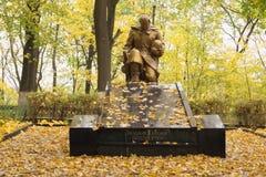 Die Skulptur eines knienden Soldaten am Standort ein Massengrab von Stockbild