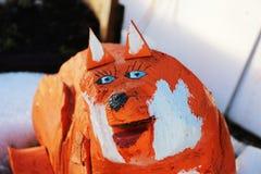 Die Skulptur eines lustigen hölzernen Fuchses steht im Garten für Dekoration Lizenzfreies Stockbild
