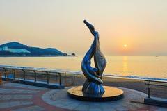 Die Skulptur im Strandsonnenaufgang Stockfotos