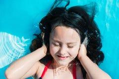 Die smilling Mädchenlügen im Pool mit seinen Händen bedeckt die Ohren und die Augen lizenzfreies stockbild
