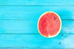 die Sommerwassermelone ist Scheibe der Hälfte auf einem blauen rustikalen Holz-BAC Lizenzfreies Stockfoto