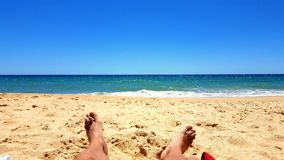 Die Sonne auf dem Sand nehmend, setzen Sie nahe dem Meer auf den Strand Stockfoto