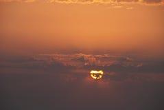 Die Sonne auf einer Abnahme in den Wolken Stockbilder