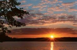 Die Sonne bricht durch die Bäume, der Sonnenuntergang, die Sonne, die im Wasser reflektiert wird Stockfoto