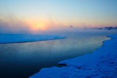 Die Sonne, die in Fluss steigt Lizenzfreie Stockbilder
