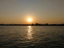 die Sonne, die mit Flussansicht aufzeichnet Stockbild