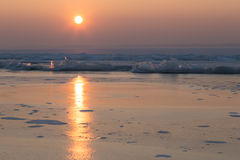 Die Sonne eingestellt über den gefrorenen See Stockbilder
