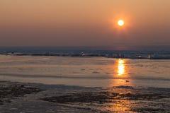 Die Sonne eingestellt über den gefrorenen See Lizenzfreie Stockfotografie