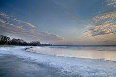 Die Sonne eingestellt über den gefrorenen See Stockbild