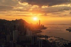 Die Sonne geht bei Hong Kong Downtown und bei Victoria Harbour unter FI lizenzfreie stockfotografie