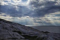 Die Sonne ` s Strahlen machen ihre Weise durch die Wolken über dem Meer und dem Felsen Lizenzfreie Stockfotografie