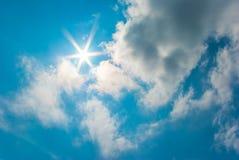 Die Sonne scheint auf blauem Himmel und Wolken. Lizenzfreies Stockfoto