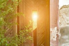 Die Sonne scheint durch das Fenster in der alten Tür stockbilder
