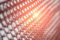 Die Sonne scheint durch das rostige Gitter, die Beschaffenheit des Gitters für den Hintergrund stockfotos