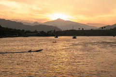 Die Sonne stellt hinter den Berg ein und beleuchtet herauf die letzten Strahlen eines Fischerbootes, das in einer tropischen Buch lizenzfreie stockbilder