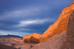 Die Sonne stellt wunderbar auf felsige Klippen im Mondtal in der atacama Wüste ein, wenn bewölkt durch einen stürmischen Himmel Lizenzfreies Stockbild