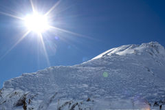 Die Sonne und eine Spitze im Hoch der Berge Stockbild