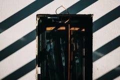 Die Sonne wirft über der weißen Betonmauer Stockfoto
