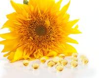 Die Sonnenblume und die Kapseln mit Vitaminen A und E Lizenzfreie Stockfotos
