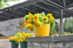 Die Sonnenblumen in einem gelben Vase auf einem konkreten Geländer Stockfotos