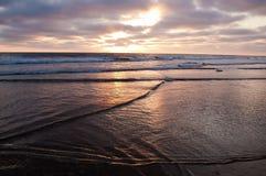 Die Sonneneinstellung über dem Pazifischen Ozean gesehen von einem Strand lizenzfreies stockbild