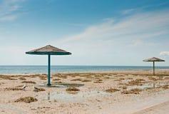 Die Sonnenschirme und zwei Seemöwen auf leerem sandigem Strand Stockfoto