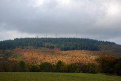 Die Sonnenstrahlen machen ihre Weise durch die dunklen Wolken und belichten das rote Herbstfeld lizenzfreie stockbilder