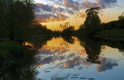 Die Sonnenuntergang-Wolken, die im Fluss reflektiert werden, steigen, Karren ansteigen auf an Stockbild